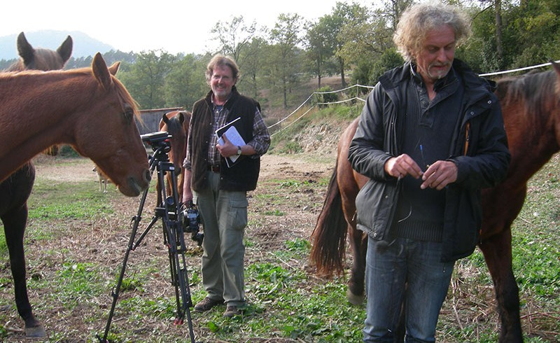 Two men and a camera amongst horses